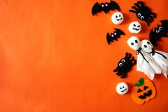 Top view of Halloween crafts, orange pumpkin, ghost and spider on orange background. With copy space for text. halloween concept stock image