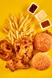Top view hamburger, french fries and fried chicken on yellow background. Copy space for your text. Royalty Free Stock Photos