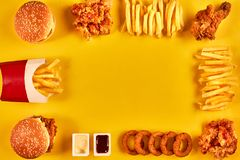 Top view hamburger, french fries and fried chicken on yellow background. Copy space for your text. Royalty Free Stock Images