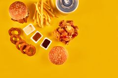 Top view hamburger, french fries and fried chicken on yellow background. Copy space for your text. Royalty Free Stock Image