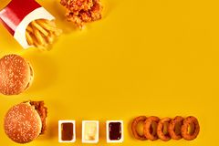 Top view hamburger, french fries and fried chicken on yellow background. Copy space for your text. Stock Images