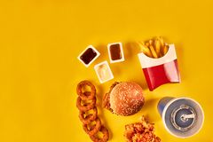 Top view hamburger, french fries and fried chicken on yellow background. Copy space for your text. Royalty Free Stock Photography