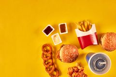 Top view hamburger, french fries and fried chicken on yellow background. Copy space for your text. Stock Image
