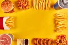 Top view hamburger, french fries and fried chicken on yellow background. Copy space for your text. Stock Photos