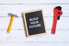 Build your future. Top view of hammer,wrench and blackboard written with & x27;BUILD YOUR FUTURE& x27; on white wooden background stock image
