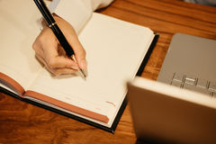 Top view. hand of businessman hold pen write on notebook. comput. Top view. hand of businessman hold pen write on blank notebook. computer notebook placed beside Royalty Free Stock Photo