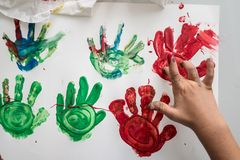 Hand of a child making red and green colourful palm prints. Top view of a hand of a child making red and green colourful palm prints on a piece of white paper stock photo