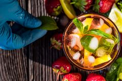 Hand adds mint to homemade srawberry mojito. Top view hand in glove adding mint leaf to glass of strawberry lemonade with lemon royalty free stock photography