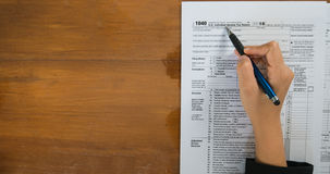Top view of hand hold pen fill in the details on the tax forms paper in business concept. stock image
