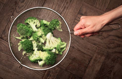 Top view of a hand holding a strainer with cut broccoli Royalty Free Stock Photography