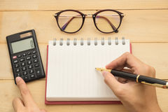 Top view. hand using ballpoint pen writing on empty notebook pap. Er have black calculator put on beside and have glasses put on top. wooden are background. this Stock Image