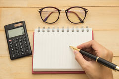 Top view. hand using ballpoint pen writing on empty notebook pap. Er have black calculator put on beside and have glasses put on top. wooden are background. this Stock Photo