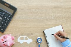 Top view of hand writing about car insurance concept with stethoscope, car pager, piggy bank, calculator and notepad. royalty free stock images