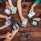 Top view hands circle using phone in cafe - Multiracial friends mobile addicted interior scene from above - Wifi connected people Stock Image
