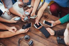 Top view hands circle using phone in cafe - Multiracial friends mobile addicted interior scene from above - Wifi connected people Stock Photo
