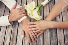 Top view of bride and groom hands with the engagement rings, and bouquet of white callas on rustic wooden table background. Outdoor Royalty Free Stock Photos
