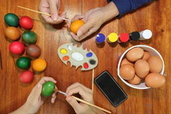 Top view of hands of family christian members are holding eggs and paint prepare easter day. Royalty Free Stock Photo