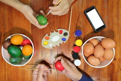 Top view of hands of family members are painting eggs with a paintbrush on wooden table for preparing  Easter day. Happy family ti Royalty Free Stock Photos