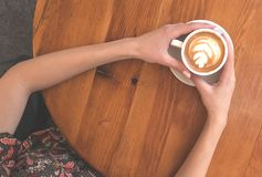 Top view of hands holding a cup of coffee. stock images