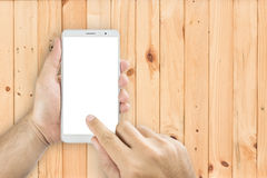 Top view hands holding smart phones. Top view hands holding smart phones on wooden table Royalty Free Stock Images