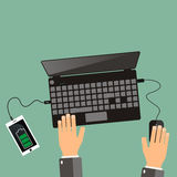 Top view. hands and laptop with connected smartphone.  Royalty Free Stock Photography