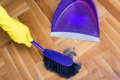 House keeper sweeping with dust pan. Top view of hands with protective gloves sweeping dirt from parquet floor with dust pan stock photography