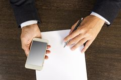 Top view of the hands with smartphone and pen on wooden table with man paper in a business suit. Top view of the hands with smartphone and pen on wooden table Royalty Free Stock Image