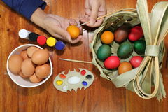 Top view of hands of young christian man painting easter eggs with a paintbrush on wooden top. Stock Photos