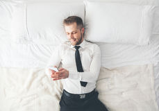 Top view. Handsome businessman lying on bed texting from his smartphone. Top view. Young handsome businessman lying on the bed texting from his smartphone Royalty Free Stock Photography