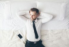 Top view. Handsome businessman relaxing on bed after a tough day at work. Top view. Young handsome businessman relaxing on bed after a tough day at work Stock Image