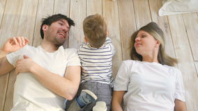 Top view of handsome father and mother play and hug their little son while lying on the floor stock footage