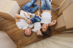 Top view of handsome father and mother play and hug their little son while lying on the floor. family relaxing and laughing after. Happy family moves into a new Stock Images