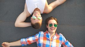 Top view of handsome gay boys in sunglasses lying on rooftop of high-rise building and laughing. Young happy male couple. Looking at camera and showing stock video