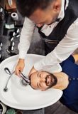 A top view of hipster man client visiting haidresser and hairstylist in barber shop. stock image
