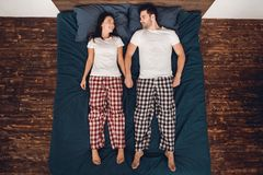 Top view. Handsome man and beautiful woman in pajama lie straight on bed and look at each other. Top view. Handsome men and beautiful women in pajama lie Royalty Free Stock Image