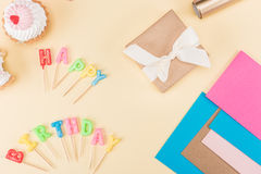 Top view of happy birthday lettering, envelope with ribbon, cakes and colorful cards on pink. Birthday party concept royalty free stock image