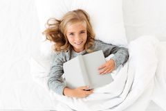 Top view of happy blonde girl lying in bed with gray book, looki. Ng at camera Stock Photography