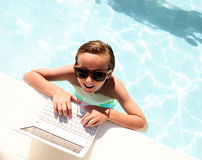 Top view of happy boy with laptop in swimming pool. Top view of happy little Caucasian boy wearing sunglasses standing in swimming pool, using laptop, looking at Stock Photography