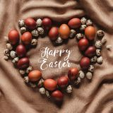 Top view of Happy Easter inscription in heart shaped frame made of chicken. And quail eggs stock photos