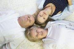 Family lies on the floor head for each other. Top view of happy family of 3 bonding to each other heads and smiling while lying on the h floor Stock Photography