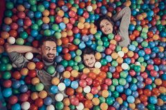 Top view. Happy family lying in pool with balls royalty free stock image