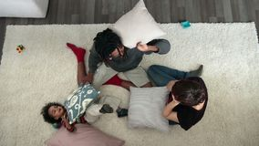 Top view of happy family pillow fighting on carpet stock video