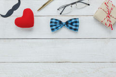 Top view Happy Father day. Accessories with red heart,mustache,vintage bow tie,present,pen on rustic white wooden background Royalty Free Stock Photography