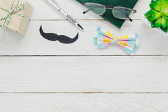 Top view Happy Father day.accessories with tree. Top view Happy Father day.accessories with tree,mustache,vintage bow tie,present,pen ,note book, and eyeglasses Royalty Free Stock Photography