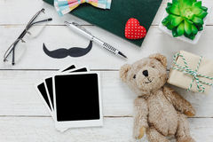 Top view Happy Father day. Blank photo for free text and accessories with tree,mustache,vintage bow tie,present,pen ,note book, and bear doll on rustic white Stock Photography