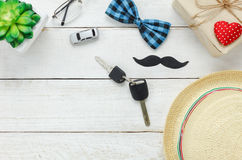 Top view Happy Father day.Key with car for gift to father. Accessories with red heart,mustache,vintage bow tie,present,hat and tree on rustic white wooden Royalty Free Stock Photo