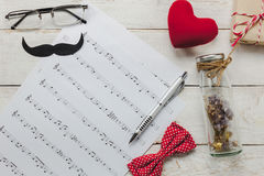 Top view Happy Father day with music concept. Music note paper on rustic wooden background.accessories with red heart,gift,mustache,vintage bow tie,dried flower Royalty Free Stock Photography
