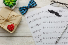 Top view Happy Father day with music concept. Music note paper on rustic wooden background.accessories with red heart,gift,mustache,vintage bow tie,tree and Royalty Free Stock Photo
