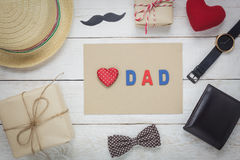 Top view Happy Father day . Red heart and word `DAD` on paper.accessories with mustache,vintage bow tie,wallet,hat,present and watch rustic wooden background Royalty Free Stock Photography