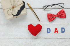 Top view Happy Father day . Red heart and word `DAD` on rustic wooden background. accessories with mustache,vintage bow tie,pen,present and eyeglasses Stock Photography